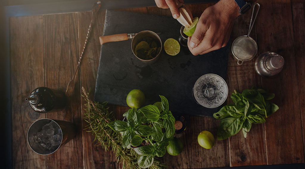 birds eye view of man making cocktails with fresh herbs