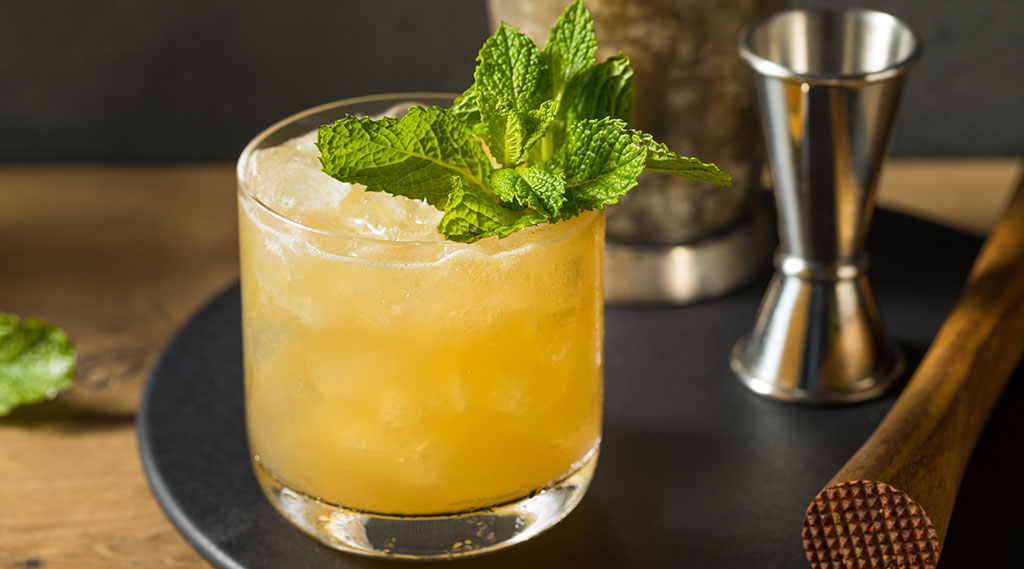 orange cocktail with mint sprig