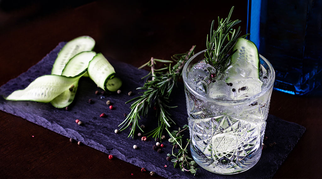 cocktail with fresh rosemary, peppercorns and cucumber