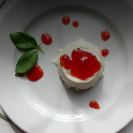panna cotta on a plate with fresh basil