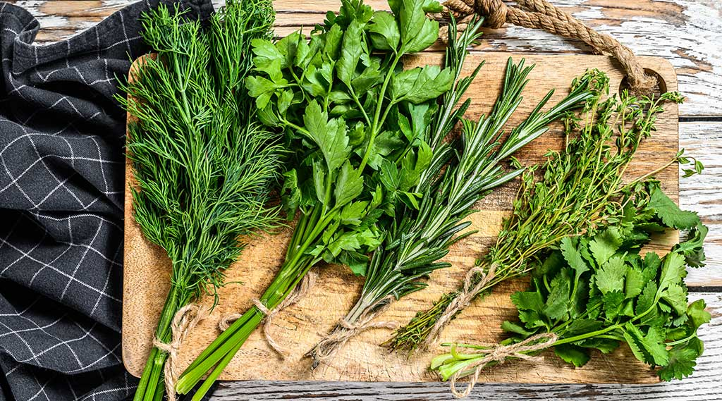 Bunches of herbs on a wooden chopping board - we provide bespoke service to our wholesale and retail customers