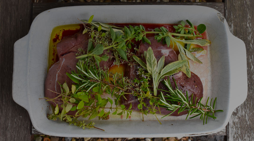Two wild boar marinated steaks with fresh herbs