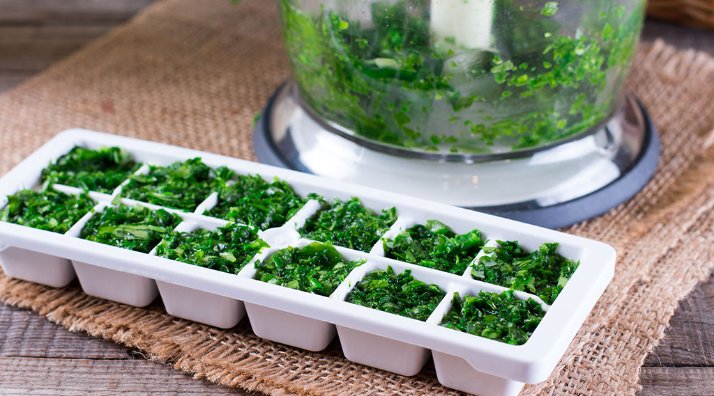 chopped up fresh herbs in ice cube tray